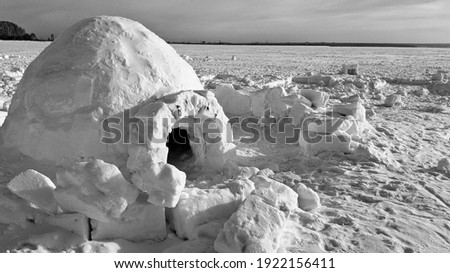 igloo and snow shelter in high snowdrift with mountains peaks on background