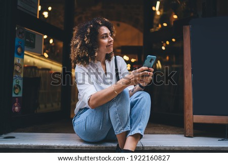 Pretty Caucaisan woman with modern cellphone device in hands resting at touristic street sitting outdoors and smiling, charming hipster girl holding smartphone technology for network and looking away Royalty-Free Stock Photo #1922160827