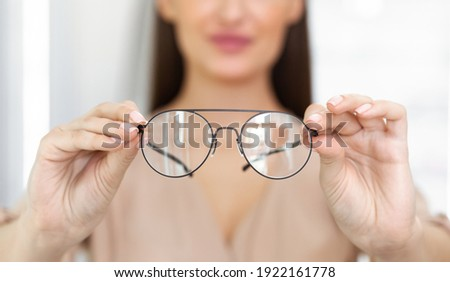 Eyesight And Vision Concept. Closeup of unrecognizable woman showing new eyeglasses to camera, standing at optics store, blurred background, selective focus on eyewear. Lady offering specs Royalty-Free Stock Photo #1922161778