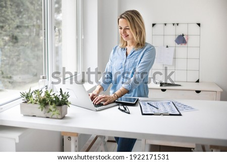 Businesswoman working at a standing desk in office