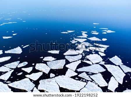 Ice melting in blue sea water