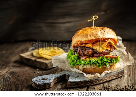 Homemade burger with grilled beef meat, vegetables, sauce on rustic wooden background. fast food and junk food concept.