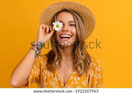 beautiful attractive stylish woman in yellow dress and straw hat holding daisy flower romantic mood posing on yellow background isolated in love summer fashion trend style, natural look Royalty-Free Stock Photo #1922207963