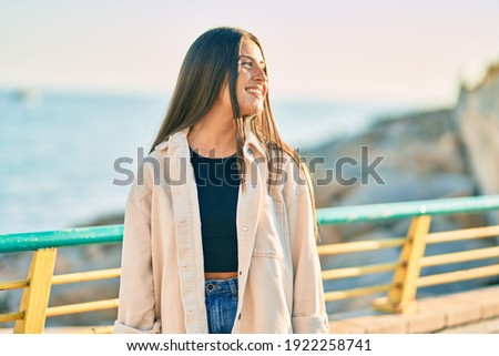 Young hispanic girl smiling happy standing at the promenade.