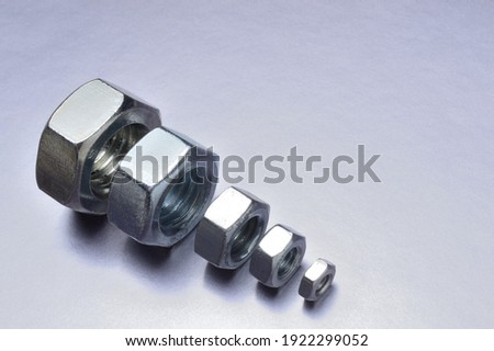 five new chrome nuts of different sizes from large to small are lined up. metallic background. close-up.