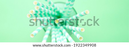 pile of paper striped white and green drinking straws for party in clear glass cup on green background. banner Royalty-Free Stock Photo #1922349908
