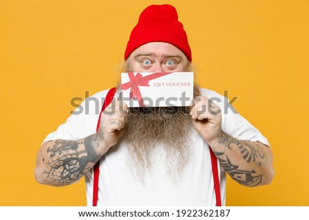 Fat pudge obese chubby overweight tattooed blue-eyed bearded fun man 30s has big belly in white t-shirt red hat covering face with gift voucher flyer card mock up isolated on yellow background studio