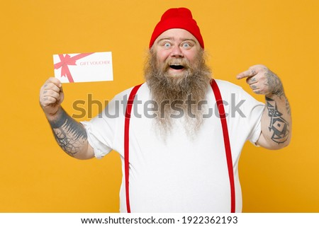Fat pudge obese chubby overweight tattooed bearded overjoyed caucasian man 30s has big belly in white t-shirt red hat suspenders hold gift voucher flyer mock up isolated on yellow background studio