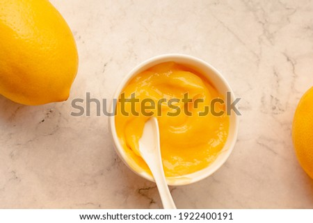 Delicious homemade tangy lemon curd decorated with fresh fruit on marble background.Top view. Royalty-Free Stock Photo #1922400191