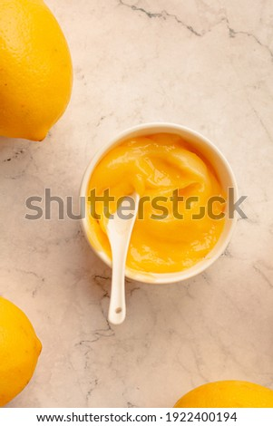 Delicious homemade tangy lemon curd decorated with fresh fruit on marble background.Top view. Royalty-Free Stock Photo #1922400194