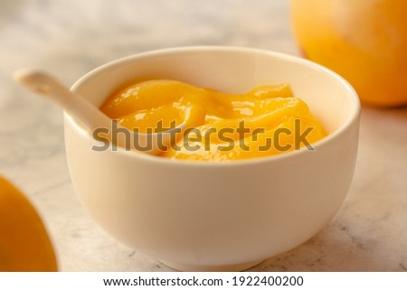 Composition with delicious Yellow lemons and Lemon curd in a sausepan white bowl on marble background. Royalty-Free Stock Photo #1922400200