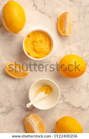 Delicious homemade tangy lemon curd decorated with fresh fruit on marble background.Top view. Royalty-Free Stock Photo #1922400206