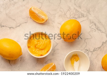 Homemade tangy lemon curd decorated with fresh fruit on marble background.Top view. Copy space for text. Royalty-Free Stock Photo #1922400209