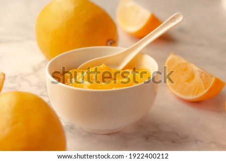 Homemade fresh pudding or tangy lemon curd in a white bowl.Selective focus. Royalty-Free Stock Photo #1922400212