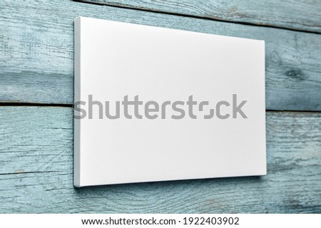 White canvas hanging on light blue wooden wall. Mockup, wall decor, blank canvas stretched on stretcher bar, side view Royalty-Free Stock Photo #1922403902