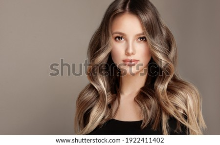Beauty  girl with long  and   shiny wavy  Hair ,coloring and toning, shatush and balayash .  Beautiful   woman model with curly hairstyle . Royalty-Free Stock Photo #1922411402