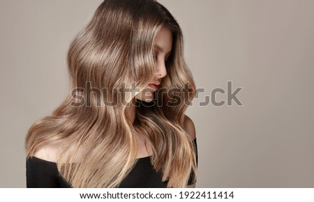 Beauty  girl with long  and   shiny wavy  Hair ,coloring and toning, shatush and balayash .  Beautiful   woman model with curly hairstyle . Royalty-Free Stock Photo #1922411414