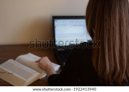 Closeup of a translator working with CAT (Computer-Assisted Translation) tool and dictionary.