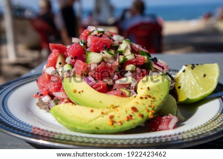 Tuna Ceviche Tostada served with avocado and lime on the beach in Mexico Royalty-Free Stock Photo #1922423462