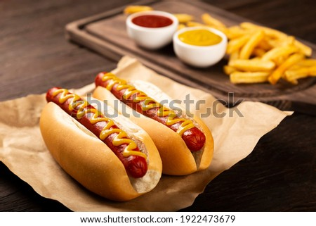 Hot dogs with ketchup, yellow mustard, fries and soda. Image with selective focus Royalty-Free Stock Photo #1922473679