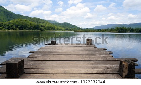 Panoramic view of Wooden bridge lake with Green mountain, bright blue sky and lake at the background with Empty wooden floor. can be used for display product Mock Up. Panoramic Nature Scene. Royalty-Free Stock Photo #1922532044