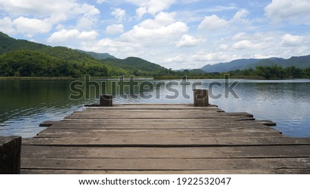 Panoramic view of Wooden bridge lake with Green mountain, bright blue sky and lake at the background with Empty wooden floor. can be used for display product Mock Up. Panoramic Nature Scene. Royalty-Free Stock Photo #1922532047