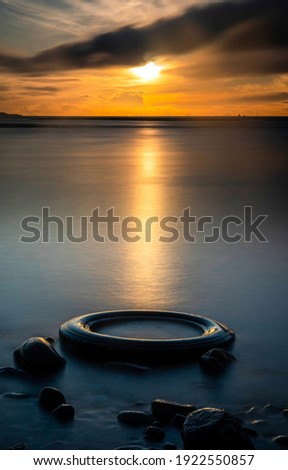 Tire in sunset water. Sunset water view. Tire in sunset water view. Sunset water scene Royalty-Free Stock Photo #1922550857