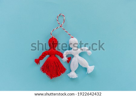 Martisor talisman on blue background. Traditional accessory for holiday of early spring in Romania and Moldova. Flat lay.