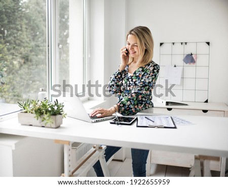 Businesswoman telephoning using cellphone while working at ergonomic standing desk. Royalty-Free Stock Photo #1922655959