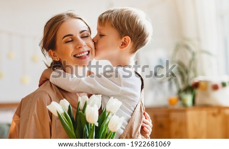 tender son kisses the happy mother and gives her a bouquet of tulips, congratulating her on mother's day during holiday celebration at home Royalty-Free Stock Photo #1922681069