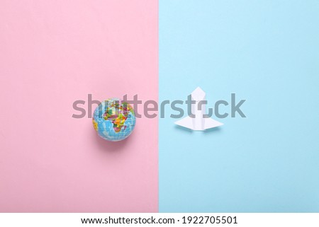 Origami space rocket shuttle and globe on pink blue background. Space flight concept. Minimalism