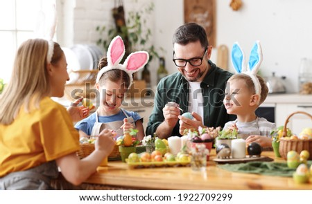 Joyful family wearing bunny ears headbands gathering at table in modern light kitchen and paining Easter eggs together Royalty-Free Stock Photo #1922709299