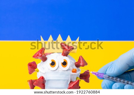 Hand of medical worker holding syringe with vaccine against Covid-19, ukrainian flag in the background. Cartoon model of coronavirus in the foreground, scared to get an injection.