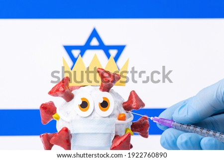 Animated coronavirus model with crown and medical mask with a flag of Israel in background. Hand of a doctor holding syringe with vaccine against Covid-19 virus.