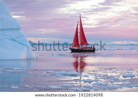 Beautiful little red sailboat in the arctic next to a massive iceberg showing the scale in pink dawn light. Ilulissat, Disko Bay, Greenland. Royalty-Free Stock Photo #1922814098