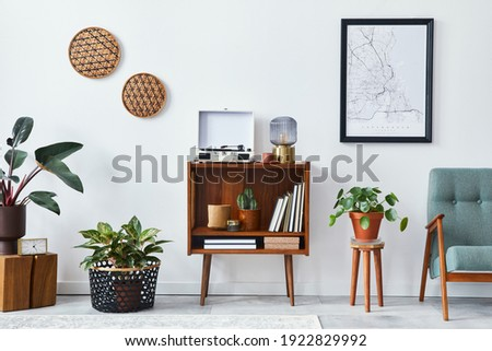 Retro composition of living room interior with mock up poster map, wooden shelf, book, armchair, plant, cacti, vinyl recorder, decoration and personal accessories in stylish home decor. Royalty-Free Stock Photo #1922829992