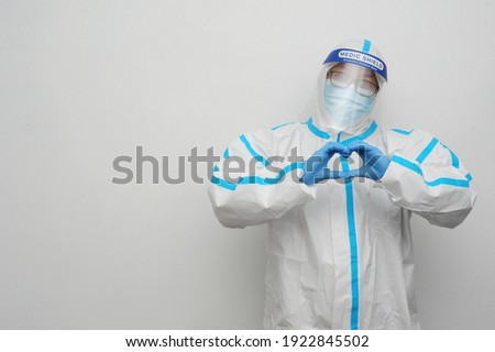 Frontliner in happy mood showing love hand sign in hazmat suit wearing transparent protective shield handling Covid-19 situation with white clean background and copyspace.