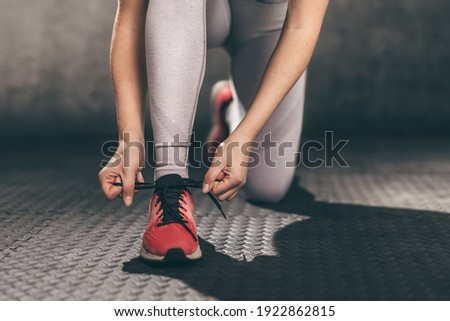 Closeup of young woman runner tying her shoelaces. Royalty-Free Stock Photo #1922862815