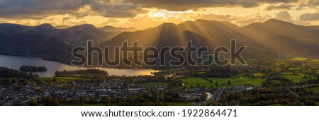 Golden rays of light breaking through clouds over Derwentwater and Keswick in the Lake District. Royalty-Free Stock Photo #1922864471