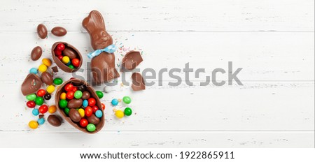 Chocolate easter eggs, choco rabbit and colorful sweets on wooden background greeting card. Top view. Flat lay with space for your greetings Royalty-Free Stock Photo #1922865911