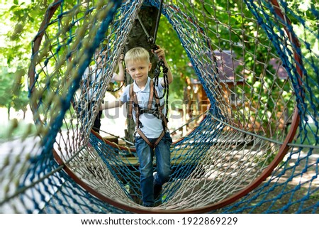 Portrait of a little boy in climbing gear in a rope park, holding a rope with a carbine. Royalty-Free Stock Photo #1922869229