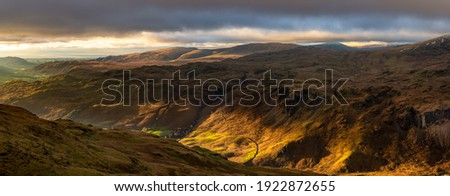 Beautiful light with panoramic view of Western Lake District fells and dramatic dark clouds in the sky. Royalty-Free Stock Photo #1922872655