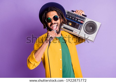 Photo of excited funky gut hold boom box mic singing enjoy free time isolated on magenta color background