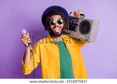 Portrait of positive dark skin person front teeth gap smile hold boom box mic isolated on purple color background
