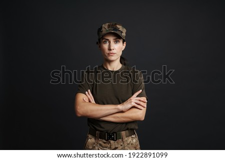 Confident beautiful soldier woman standing isolated over black background, arms folded Royalty-Free Stock Photo #1922891099
