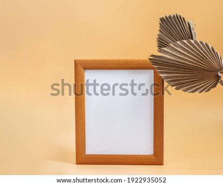 Picture frame and dry sugar palm leaves on the beige neutral background closeup. Mockup template with blank for displaying your picture or any design.