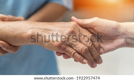 Parkinson disease patient, Alzheimer elderly senior, Arthritis person's hand in support of nursing family caregiver care for disability awareness day, National care givers month, aging society concept Royalty-Free Stock Photo #1922957474