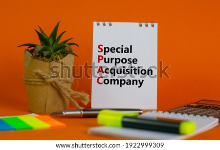 SPAC, special purpose acquisition company symbol. White note with words 'SPAC' on beautiful orange background, copy space. Business and SPAC, special purpose acquisition company concept.
