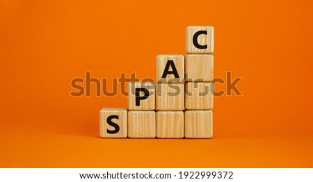SPAC, special purpose acquisition company symbol. Businessman holds cubes with word 'SPAC' on beautiful orange background, copy space. Business and SPAC, special purpose acquisition company concept.