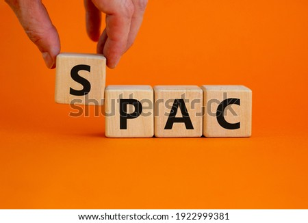 SPAC, special purpose acquisition company symbol. Wooden cubes with word 'SPAC' on beautiful orange background, copy space. Business and SPAC, special purpose acquisition company concept.